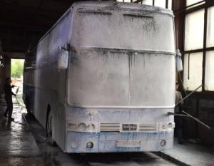 Автобус в пене, мойщики обрабатывают поверхность щетками - фото.